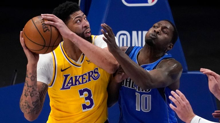 Los Angeles Lakers' Anthony Davis (3) works against Dallas Mavericks' Dorian Finney-Smith (10) and Luka Doncic, right, for a shot in the first half of an NBA basketball game in Dallas, Thursday, April 22, 2021.