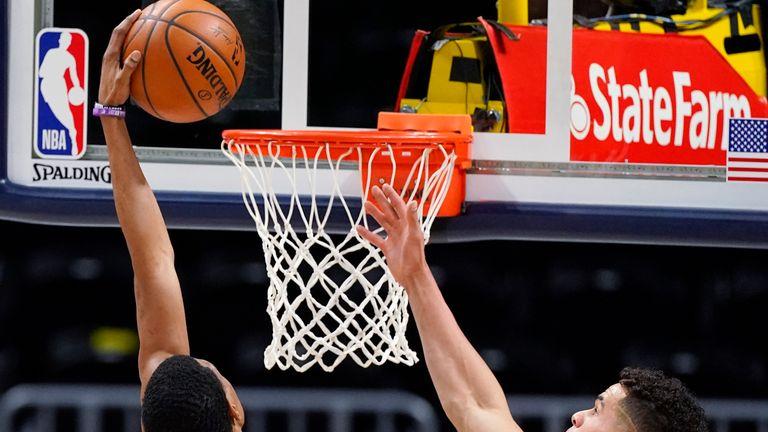 Memphis Grizzlies guard De'Anthony Melton, left, dunks the ball for a basket as Denver Nuggets forward Michael Porter Jr., defends in the second half of an NBA basketball game Monday, April 19, 2021, in Denver. (AP Photo/David Zalubowski)
