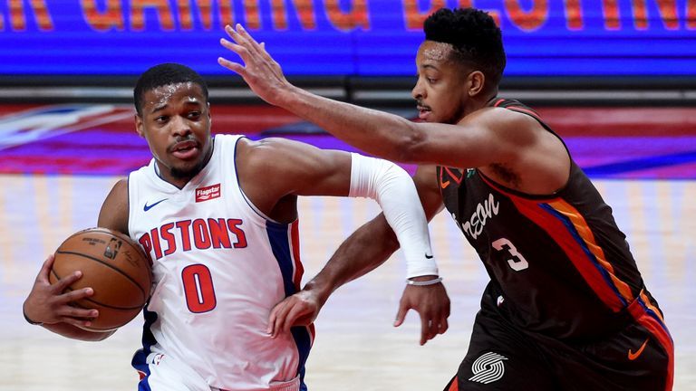 Detroit Pistons guard Dennis Smith Jr., left, drives to the basket on Portland Trail Blazers guard CJ McCollum during the first half of an NBA basketball game in Portland, Ore., Saturday, April 10, 2021.
