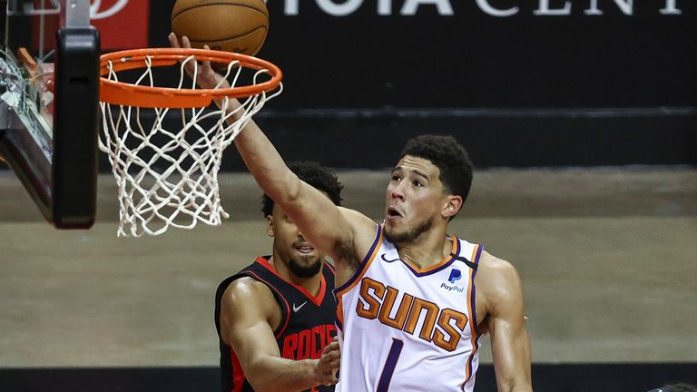 Phoenix Suns guard Devin Booker (1) shoots against Houston Rockets forward D.J. Wilson (00) during the third quarter of an NBA basketball game in Houston, Monday, April 5, 2021.