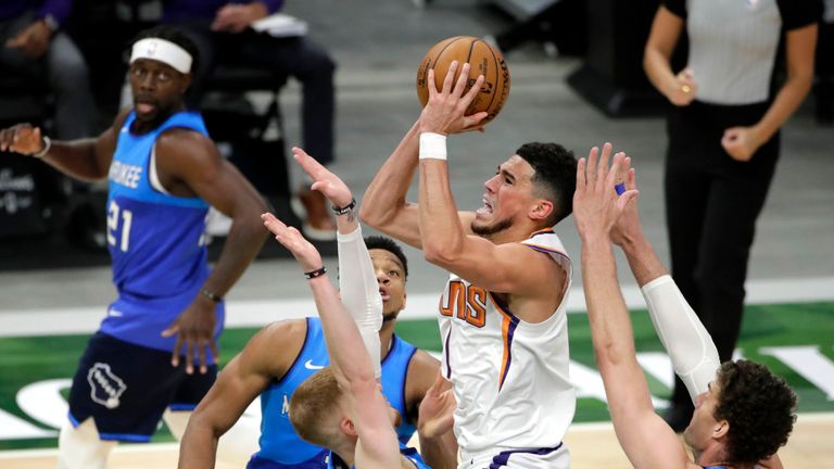 Phoenix Suns' Devin Booker, center, drives to the basket against multiple Milwaukee Bucks defenders during the second half of an NBA basketball game Monday, April 19, 2021, in Milwaukee. (AP Photo/Aaron Gash)
