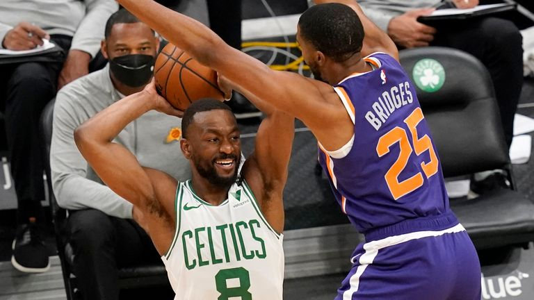 Boston Celtics guard Kemba Walker (8) passes the ball against the defense of Phoenix Suns forward Mikal Bridges (25) in the first half of an NBA basketball game, Thursday, April 22, 2021, in Boston.