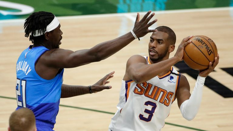 Phoenix Suns' Chris Paul, right, drives to the basket against Milwaukee Bucks' Jrue Holiday, left, during the second half of an NBA basketball game Monday, April 19, 2021, in Milwaukee. (AP Photo/Aaron Gash)