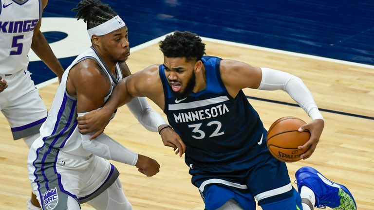 Minnesota Timberwolves center Karl-Anthony Towns (32) is fouled by Sacramento Kings center Richaun Holmes during the first half of an NBA basketball game Monday, April 5, 2021, in Minneapolis.
