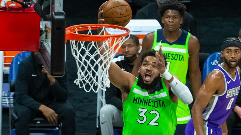 Minnesota Timberwolves center Karl-Anthony Towns (32) scores against the Sacramento Kings during the first quarter of an NBA basketball game in Sacramento, Calif., Tuesday, April 20, 2021.
