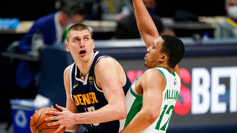 AP - Denver Nuggets center Nikola Jokic, left, turns to shoot as Boston Celtics forward Grant Williams defends