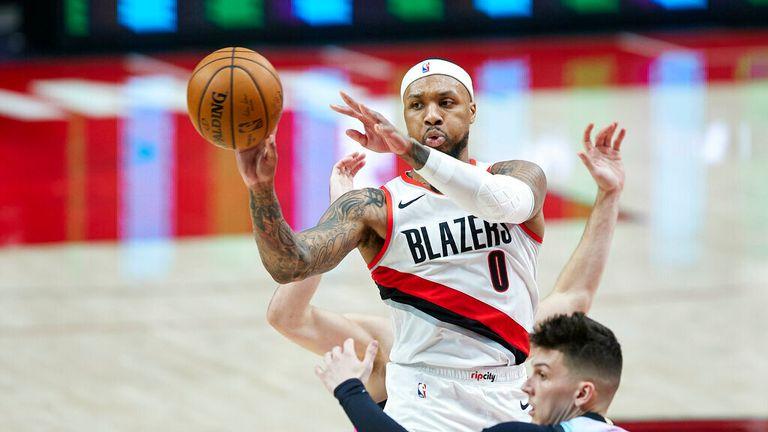 AP - Portland Trail Blazers guard Damian Lillard, top, passes the ball away from Miami Heat guard Tyler Herro