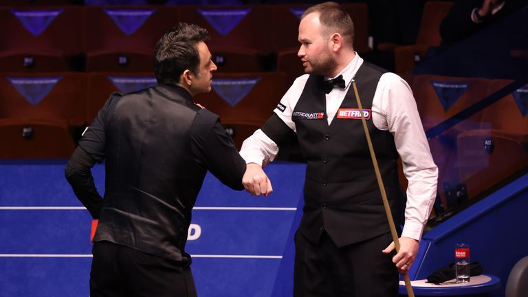 O'Sullivan (L) and Mark Joyce (R) bump elbows ahead of their first round encounter