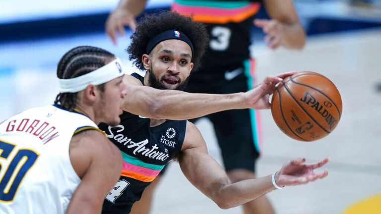 AP - San Antonio Spurs guard Derrick White (4) passes around Denver Nuggets forward Aaron Gordon (50)