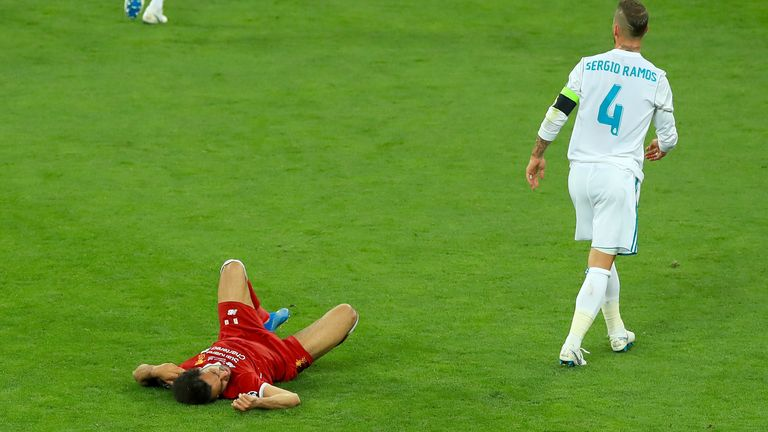 Liverpool's Mohamed Salah (left) lies injured on the pitch after a challenge from Real Madrid's Sergio Ramos during the UEFA Champions League Final