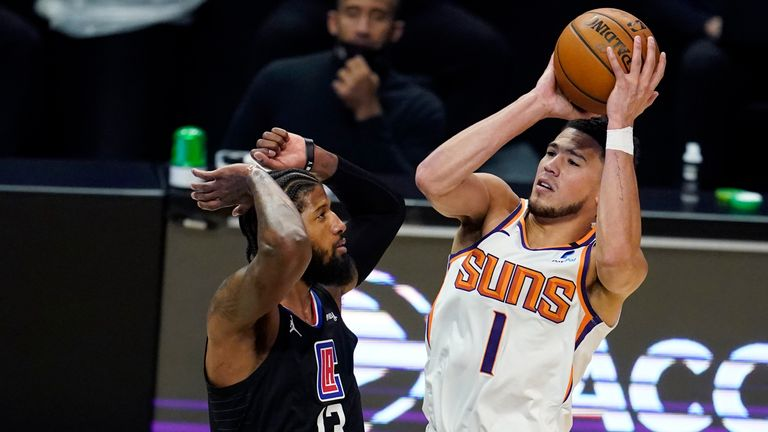 Phoenix Suns guard Devin Booker shoots over Los Angeles Clippers guard Paul George