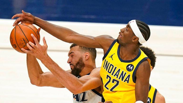 AP - Utah Jazz center Rudy Gobert, left, pulls down a rebound as Indiana Pacers guard Caris LeVert (22) defends