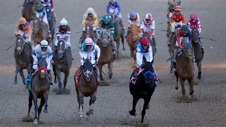Medina Spirit (red cap), ridden by jockey John Velazquez,  wins the Kentucky Derby from the front