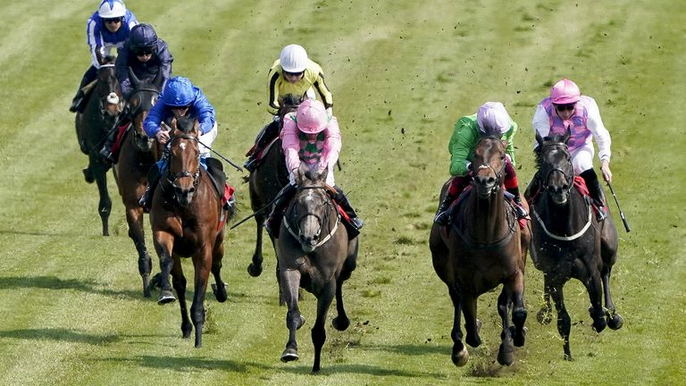 William Buick riding Wirko (left, blue) win the Blue Riband Trial at Epsom Downs