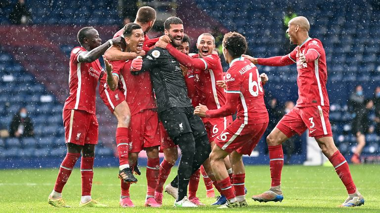 Alisson celebrates his late winner against West Brom with teammates