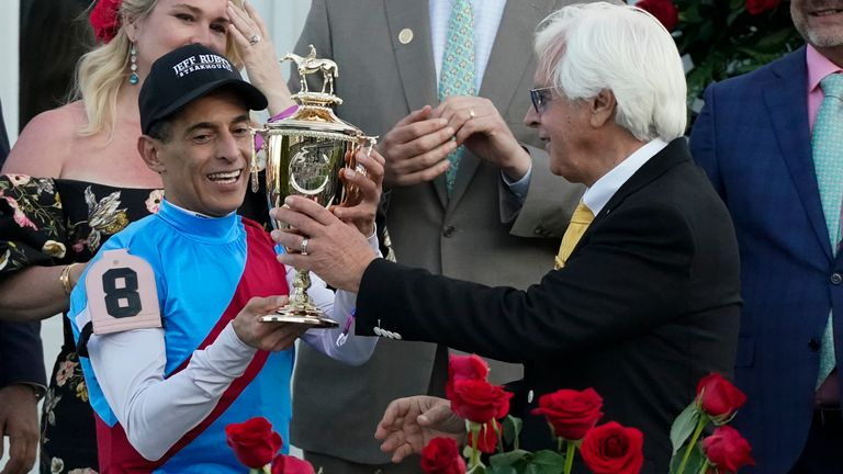 Trainer Bob Baffert hands the winner's trophy to jockey John Velazquez after they victory with Medina Spirit in the 147th running of the Kentucky Derby at Churchill Downs, Saturday, May 1, 2021, in Louisville, Ky. (AP Photo/Jeff Roberson)