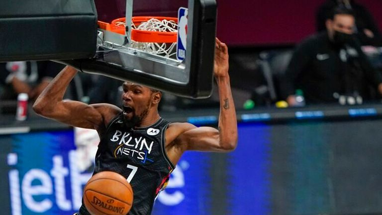 Brooklyn Nets' Kyrie Irving (11) reacts as Kevin Durant (7) dunks the ball during the first half of an NBA basketball game against the Cleveland Cavaliers Sunday, May 16, 2021, in New York. (AP Photo/Frank Franklin II)