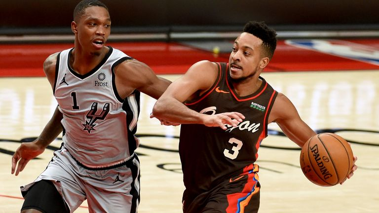 Portland Trail Blazers guard CJ McCollum, right, drives to the basket on San Antonio Spurs guard Lonnie Walker IV, left, during the second half of an NBA basketball game in Portland, Ore., Saturday, May 8, 2021. The Blazers won 124-102. (AP Photo/Steve Dykes)..