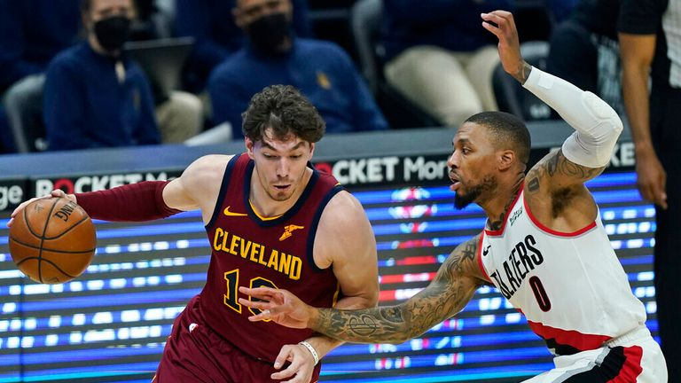 Cleveland Cavaliers' Cedi Osman (16) drives against Portland Trail Blazers' Damian Lillard (0) during the first half of an NBA basketball game Wednesday, May 5, 2021, in Cleveland. (AP Photo/Tony Dejak)