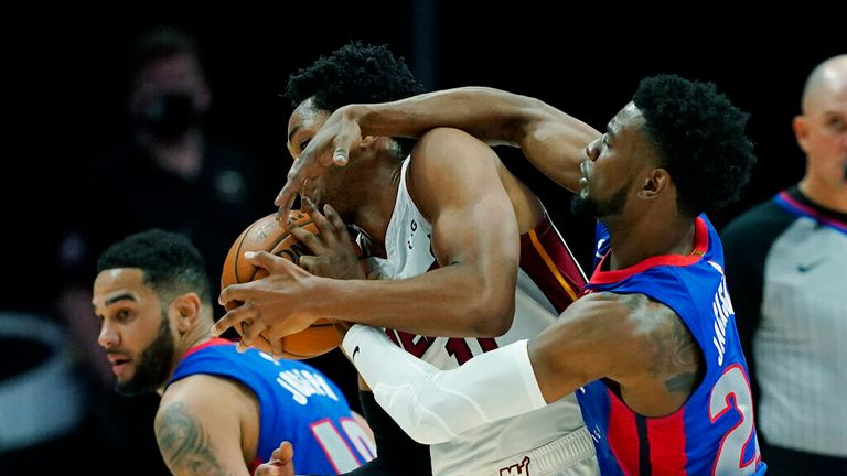 Detroit Pistons guard Josh Jackson (20) reaches in on Miami Heat forward KZ Okpala (11) during the second half of an NBA basketball game, Sunday, May 16, 2021, in Detroit. (AP Photo/Carlos Osorio)