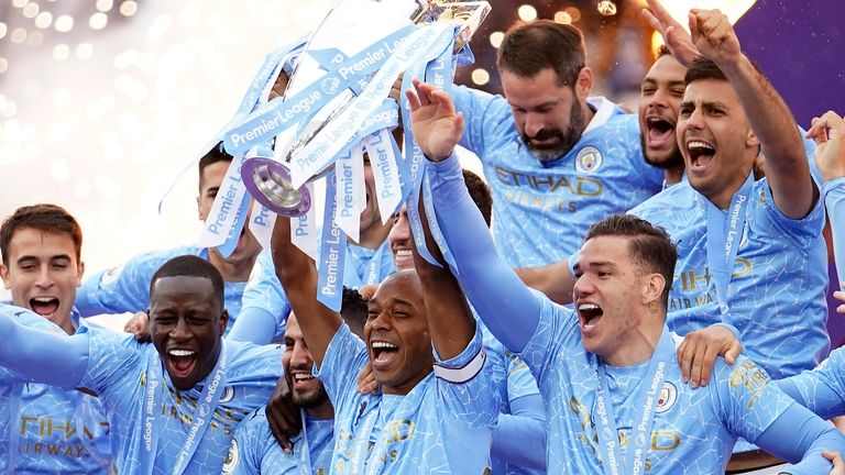 Manchester City's Fernandinho raises the trophy to celebrate winning the English Premier League title after the soccer match between Manchester City and Everton at the Etihad stadium in Manchester, Sunday, May 23, 2021.(AP Photo/Dave Thompson, Pool)