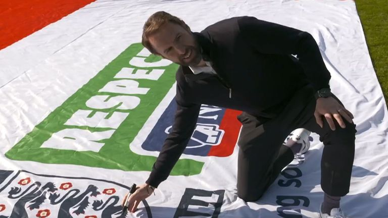 Gareth Southgate provides the first signature to the huge England flag that will tour the country