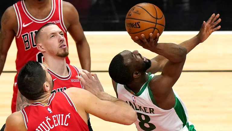 Boston Celtics guard Kemba Walker shoots as Chicago Bulls centers Nikola Vucevic and Daniel Theis watch