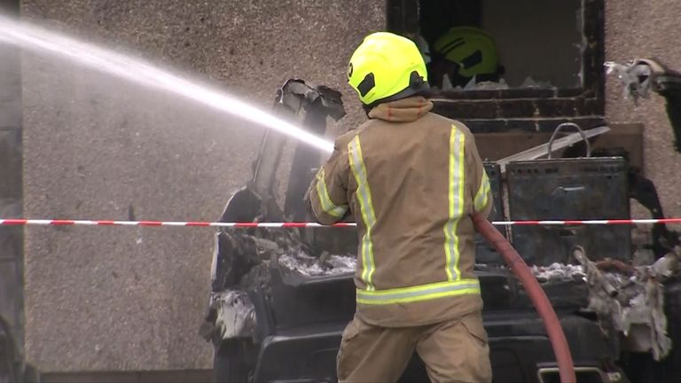 A firefighter helps extinguish the blaze in front of a burnt-out vehicle