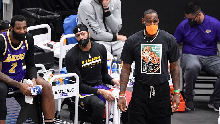 Los Angeles Lakers forward LeBron James, in orange mask, watches during the first half of an NBA basketball game against the Washington Wizards