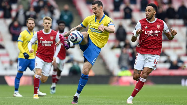 Lewis Dunk clears the ball under pressure from Pierre-Emerick Aubameyang
