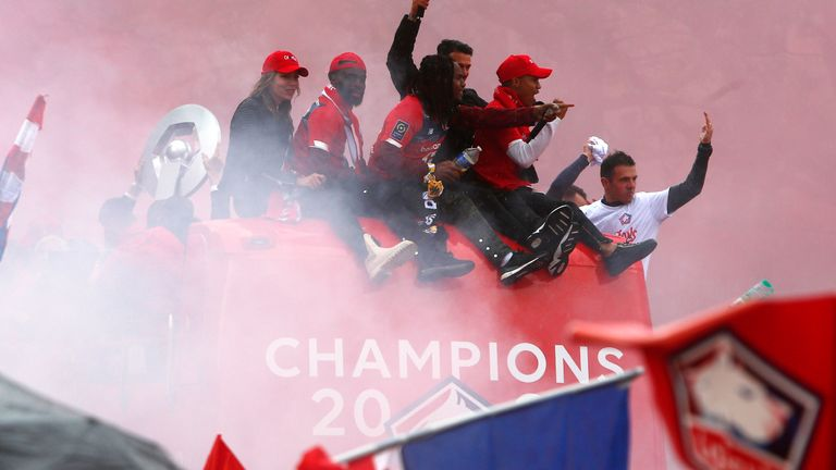 Lille players wave to fans from the top of an open top bus after winning the French League.