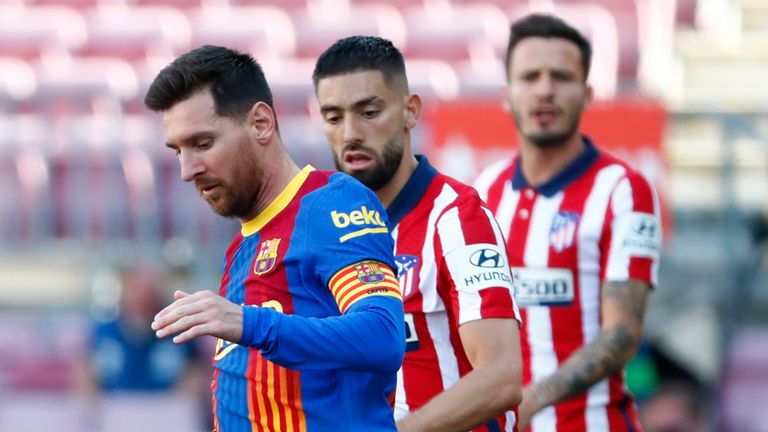 Barcelona's Lionel Messi, left, runs with the ball past Atletico Madrid's Yannick Carrasco