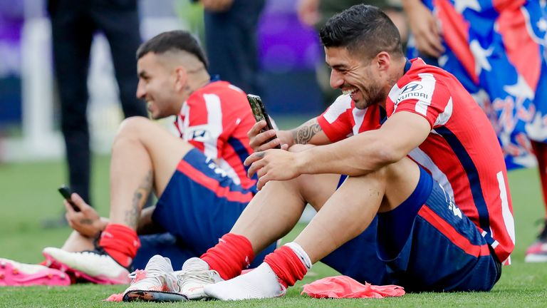 Luis Suarez on his phone after winning the La Liga title with Atletico Madrid
