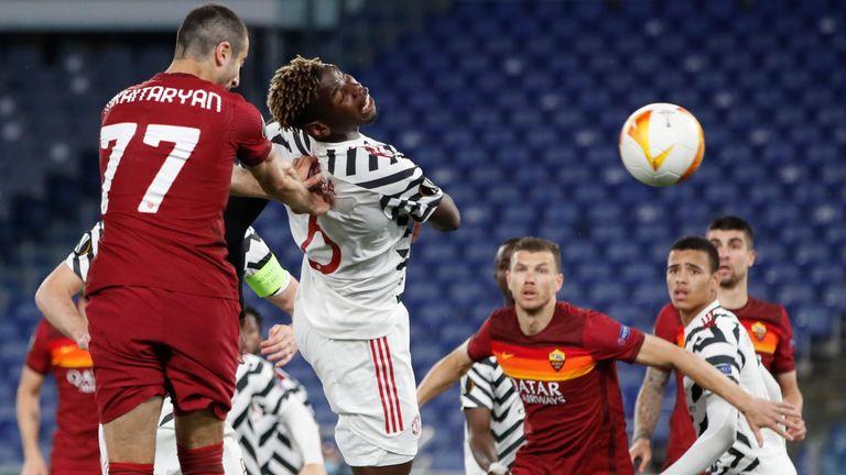 Manchester United's Paul Pogba heads the ball past Roma's Henrikh Mkhitaryan