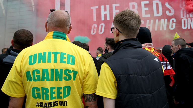"""A fan wears a shirt with a """"United Against Greed"""" message on as fans gather to protest against the Glazer family, the owners of Manchester United, before their Premier League match against Liverpool at Old Trafford, Manchester. Issue date: Sunday May 2, 2021"""