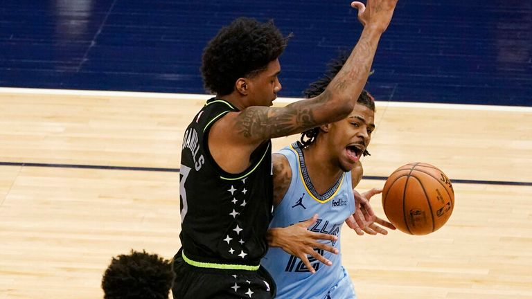 Memphis Grizzlies' Ja Morant, right, has the ball knocked out of his hands by Minnesota Timberwolves' Jaden McDaniels during the second half of an NBA basketball game Wednesday, May 5, 2021, in Minneapolis. The Grizzlies won 139-135. (AP Photo/Jim Mone)