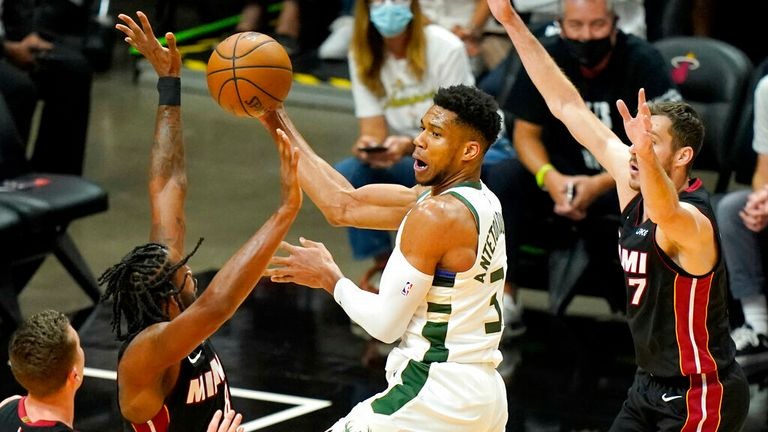 Milwaukee Bucks forward Giannis Antetokounmpo, center, drives to the basket as Miami Heat forward Trevor Ariza, left and guard Goran Dragic (7) defend during the first half of Game 4 of an NBA basketball first-round playoff series, Saturday, May 29, 2021, in Miami. (AP Photo/Lynne Sladky)