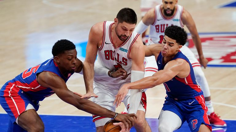Detroit Pistons forward Tyler Cook, left, and guard Killian Hayes, right, reach in on Chicago Bulls center Nikola Vucevic during the second half of an NBA basketball game, Sunday, May 9, 2021, in Detroit. (AP Photo/Carlos Osorio)