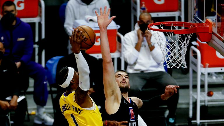 Los Angeles Lakers' Kentavious Caldwell-Pope (1) dunks against Los Angeles Clippers' Ivica Zubac (40) during the first half of an NBA basketball game, Thursday, May 6, 2021, in Los Angeles. (AP Photo/Ringo H.W. Chiu)
