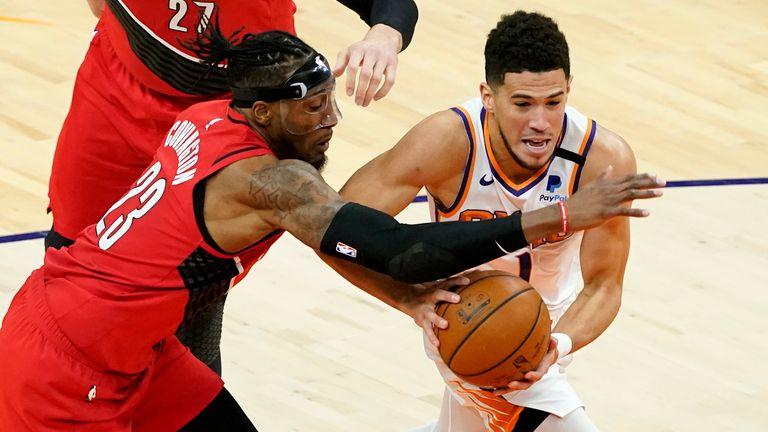 Phoenix Suns guard Devin Booker drives at Portland Trail Blazers forward Robert Covington