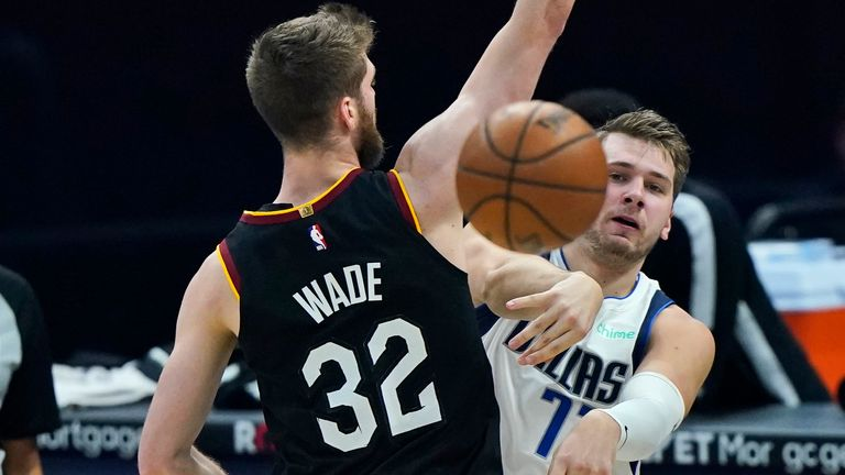 Dallas Mavericks' Luka Doncic, right, passes around Cleveland Cavaliers' Dean Wade in the first half of an NBA basketball game, Sunday, May 9, 2021, in Cleveland. (AP Photo/Tony Dejak)
