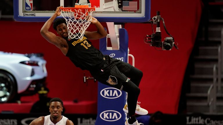 Memphis Grizzlies forward Jaren Jackson Jr. hangs on the rim after a dunk during the first half of an NBA basketball game against the Detroit Pistons, Thursday, May 6, 2021, in Detroit. (AP Photo/Carlos Osorio)
