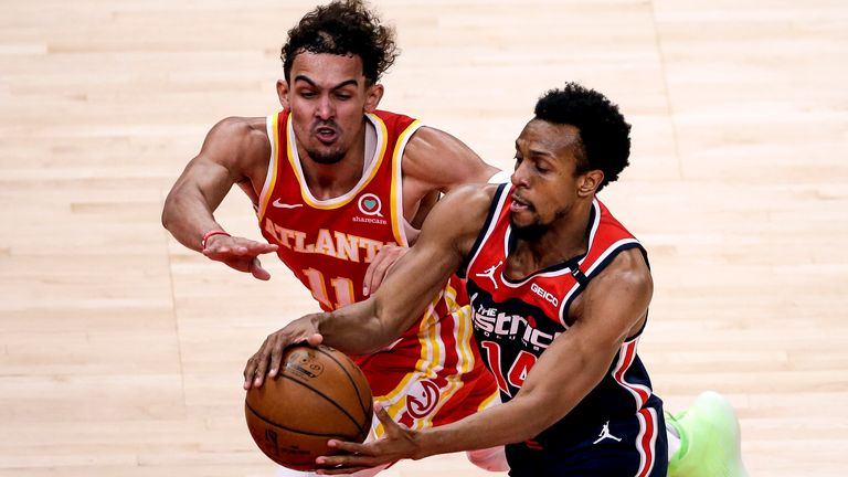 Atlanta Hawks guard Trae Young (11) tries to steal the ball from Washington Wizards guard Ish Smith (14) as they come down court during the second half of an NBA basketball game Wednesday, May 12, 2021, in Atlanta. Atlanta Hawks defeated the Washington Wizards 120-116.