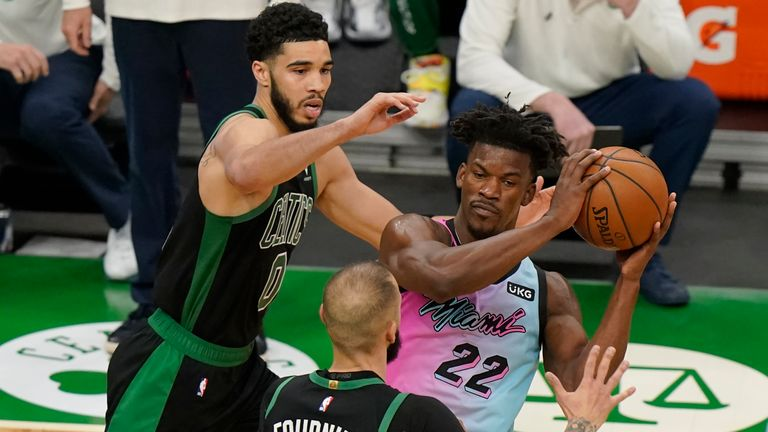Miami Heat's Jimmy Butler (22) looks for an opening around Boston Celtics' Jayson Tatum (0) and Boston Celtics' Evan Fournier, below center, in the second half of a basketball game, Sunday, May 9, 2021, in Boston. (AP Photo/Steven Senne)