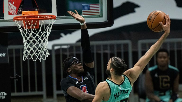 Charlotte Hornets forward Caleb Martin (10) tries to dunk the ball while guarded by Los Angeles Clippers guard Reggie Jackson (1) during the first half of an NBA basketball game in Charlotte, N.C., Thursday, May 13, 2021.