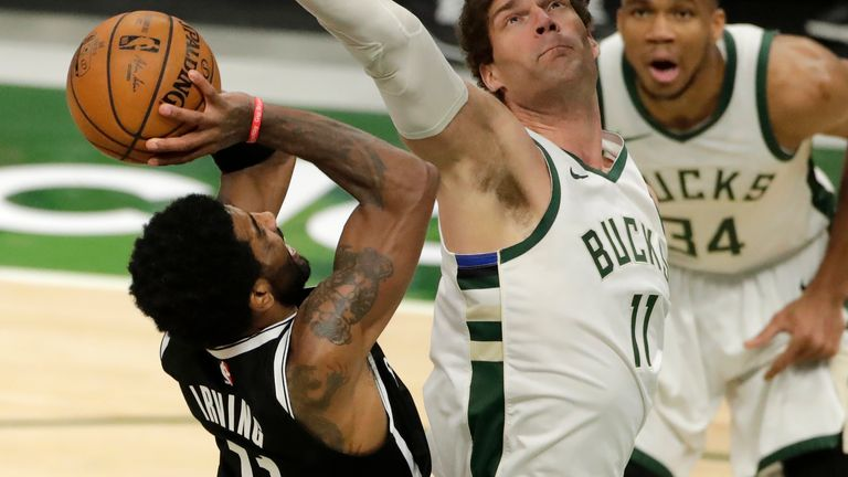 Brooklyn Nets' Kyrie Irving shoots against Milwaukee Bucks' Brook Lopez during the second half of an NBA basketball game Tuesday, May 4, 2021, in Milwaukee.