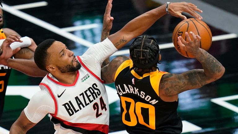 Portland Trail Blazers forward Norman Powell (24) defends against Utah Jazz guard Jordan Clarkson (00) during the first half of an NBA basketball game Wednesday, May 12, 2021, in Salt Lake City.