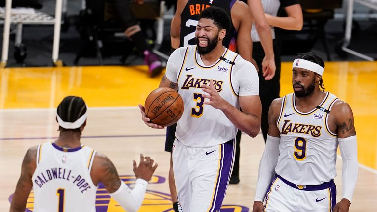 Los Angeles Lakers forward Anthony Davis (3) reacts after scoring next to teammates Kentavious Caldwell-Pope, left, Wesley Matthews (9) during the second half of an NBA basketball game against the Phoenix Suns on Sunday, May 9, 2021, in Los Angeles. (AP Photo/Marcio Jose Sanchez)