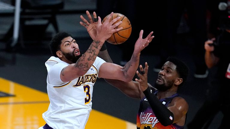 Los Angeles Lakers forward Anthony Davis (3) grabs a rebound next to Phoenix Suns center Deandre Ayton (22) during the second half of an NBA basketball game Sunday, May 9, 2021, in Los Angeles. (AP Photo/Marcio Jose Sanchez)