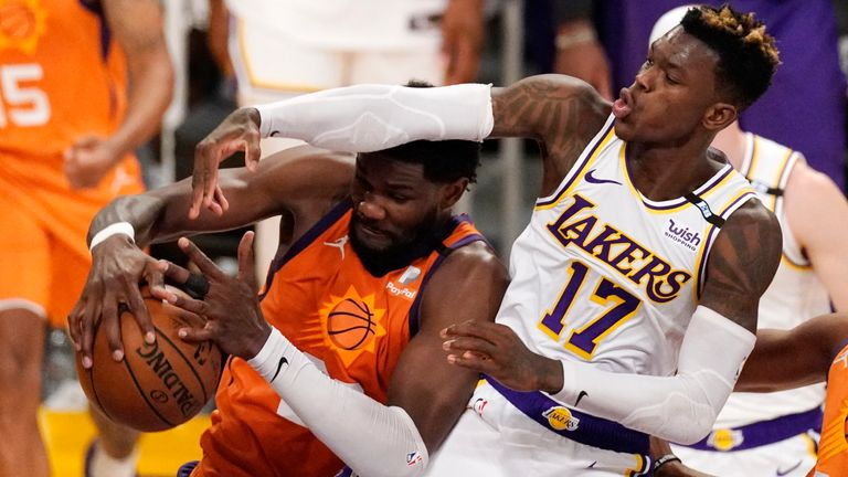 Phoenix Suns center Deandre Ayton, left, grabs a rebound away from Los Angeles Lakers guard Dennis Schroder during the second half in Game 4 of an NBA basketball first-round playoff series Sunday, May 30, 2021, in Los Angeles.